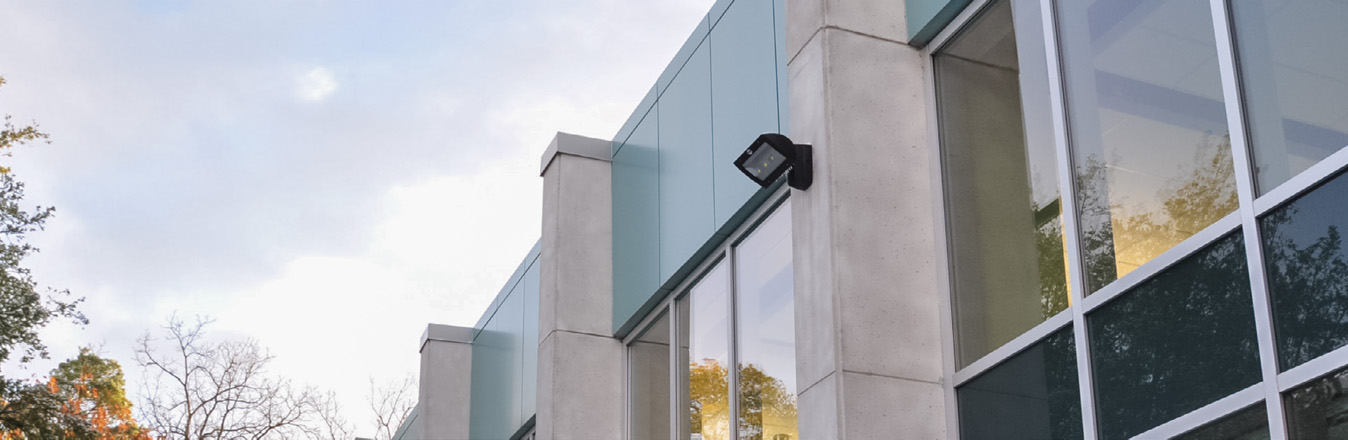 VEK-LED wall light on a white building with large windows.