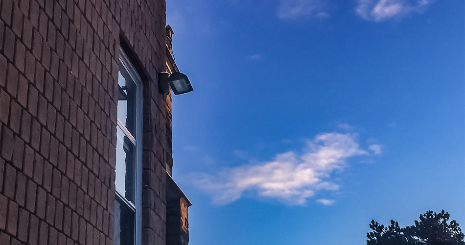 A VEK-LED wall light in mounted on the wall of a red brick building during sunset.